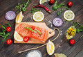 Delicious portion of fresh salmon fillet with aromatic herbs, spices and vegetables - healthy food, diet or cooking concept. Royalty Free Stock Photo