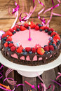 Delicious raspberry cheesecake for little girl decorated with fresh berries chocolate and candle Royalty Free Stock Photo