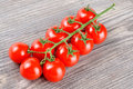 Delicious red ripe cherry tomatoes with a stem on a wooden kitchen table Stock Photography