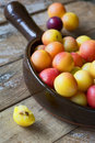 Delicious ripe plums in pan on wooden table Royalty Free Stock Photos