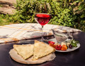 Delicious rustic crispy pie with cheese and herbs. Served on wooden plate, surrounded by glass of red wine, white sauce and ve Royalty Free Stock Photo
