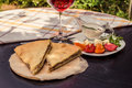Delicious rustic crispy pie with meat and herbs. Served on wooden plate, surrounded by glass of red wine, white sauce and ve Royalty Free Stock Photo