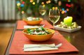 Delicious salad served for two christmas tree in the background Royalty Free Stock Photo