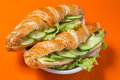 Delicious sandwich with ham and cheese tasty cucumber isolated on orange background Stock Photos