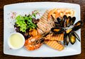 Delicious seafood dish. Fish fillet, mossels and prawn served wi Royalty Free Stock Photo