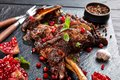 Delicious slow cooked leg of lamb with pomegranate seeds, mint leaves, spices and rosemary on a black slate plate on a wooden