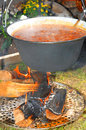 Delicious soup over open fire is simmering in a rustically iron pot image taken outside as a closeup Stock Images