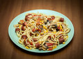 Delicious spaggetti with tomatos sausages and mashrooms corn served on wooden table special recipe in which goes through Royalty Free Stock Photo