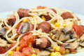 Delicious spaggetti with tomatos sausages and mashrooms corn special recipe in which goes through saugages Royalty Free Stock Photography