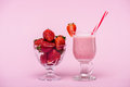Delicious strawberry milkshake in glass with straw and fresh strawberries in bowl Royalty Free Stock Photo