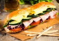 Delicious submarine sandwich stuffed with ham cheese and salad selective focus on the front part of Stock Images