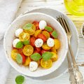 Delicious summer salad of yellow and red cherry tomatoes, mozzarella with Basil Royalty Free Stock Photo