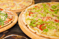 Delicious tasty pizzas with variety of toppings and cheese on wo Royalty Free Stock Photo