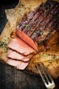 Delicious tender rare roast beef seasoned with fresh herbs and spices being carved on a wooden board on grungy oven paper overhead Stock Images