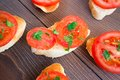 Delicious tomato bruschetta with herbs on a wooden board Stock Photo