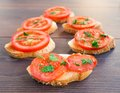 Delicious tomato bruschetta with herbs on a wooden board Stock Images