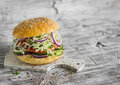 Delicious veggie burger with cabbage, tomato, cucumber, onions and peppers on a light wooden surface Royalty Free Stock Photo