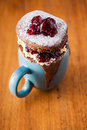 Delicious warm chocolate cake in a mug sprinkled with icing sugar and filled fresh clotted cream and whole cherry jam Stock Photography