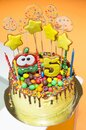 Delicious yellow cake for the birthday of a 5-year-old child, yellow stars and transparent candles on the cake, the number 5