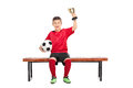Delighted boy in soccer uniform holding a trophy one hand and ball the other seated on bench isolated on white Royalty Free Stock Photography