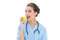 Delighted brown haired nurse in blue scrubs eating a green apple Royalty Free Stock Photo