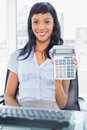 Delighted businesswoman holding a calculator in office Royalty Free Stock Photography