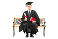 Delighted college graduate sitting on a bench and holding diploma isolated white background Stock Image