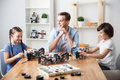 Delighted father playing with kids be closer to the children cheerful pleasant sitting at the table and looking at his who is lego Royalty Free Stock Photography