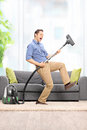 Delighted guy playing guitar on the vacuum cleaner young wand in front of a gray soda at home Royalty Free Stock Photography