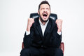 Delighted happy bearded young businessman sitting and celebrating success in black suit in office chair over white background Royalty Free Stock Images