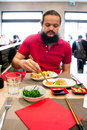 Delighted man customer in red shirt eating chinese japanese food in a restaurant Royalty Free Stock Images