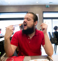 Delighted man customer in red shirt eating chinese japanese food in a restaurant with mouth wide open Royalty Free Stock Photography