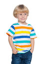 Delighted small boy is standing on the white background and looking aside Stock Image