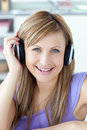 Delighted woman using headphone in the kitchen Royalty Free Stock Photography