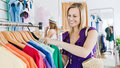Delighted young woman choosing clothes Stock Photos