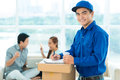 Delivery boy portrait of a smiling writing in the application form and looking at camera on the foreground Royalty Free Stock Photo