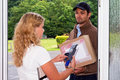 Delivery guy at the door young women pays her cash on parcel to a postal worker using a portable wireless atm Stock Images