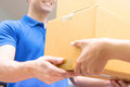 Delivery man in blue uniform handing parcel boxes to recipient Royalty Free Stock Photo