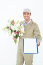 Delivery man with bouquet giving clipboard for signature portrait of happy against white background Royalty Free Stock Photography