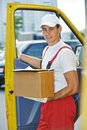 Delivery man with box postal courier in front of cargo van delivering package carton Royalty Free Stock Photo