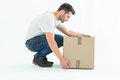 Delivery man crouching while picking cardboard box full length side view of on white background Stock Image