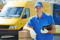 Delivery man with parcel box smiling young male postal courier in front of cargo van delivering package Royalty Free Stock Photography