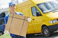 Delivery man with parcel box smiling young male postal courier in front of cargo van delivering package Royalty Free Stock Image