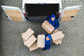 Delivery Men Carrying Cardboard Boxes Outside Truck Royalty Free Stock Photo