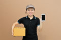 Delivery woman showing mobile phone with cardboard box