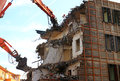 Demolished building structure with heavy machines still working Royalty Free Stock Image