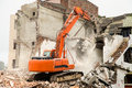 Demolition machinery destroy a old residential building Stock Photo