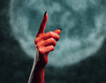 Demon hand pointing upward red with gesture on background of full moon space for text halloween or horror theme Stock Image