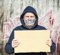 Demonstrator with a tape on a mouth and poster in hands Royalty Free Stock Photo