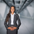 Demure businesswoman with a welcoming smile standing in the entrance to corporate building her hands clasped over her Royalty Free Stock Image